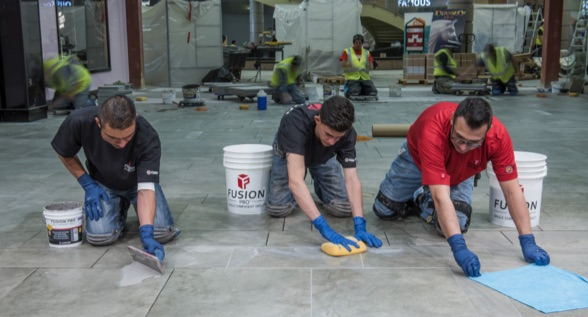 With a teamwork grouting method, one installer spreads grout across the joints, one shapes the joints with a sponge and one cleans the tile with a microfiber towel.